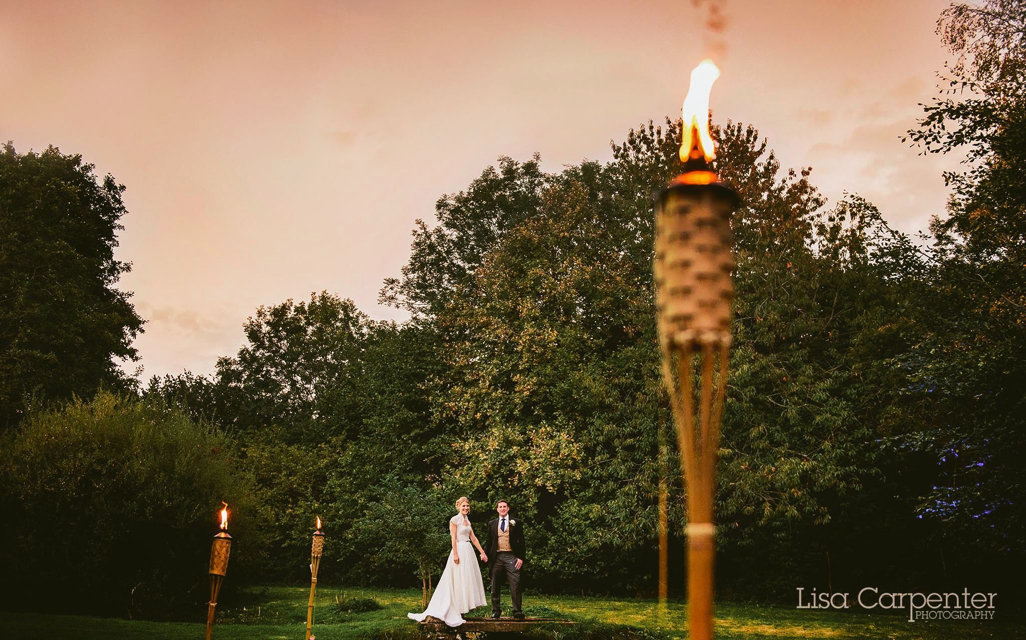 Golden Hour Portrait With Tiki Lighting For An Outdoor Top Hat And Tails Wedding Reception