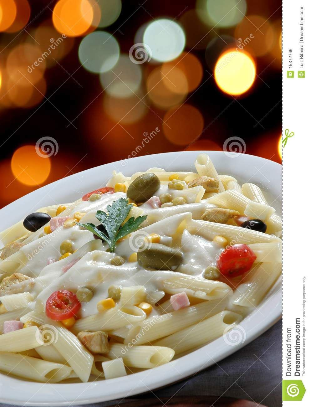 Italian cuisine, penne with white sauce and green olives.