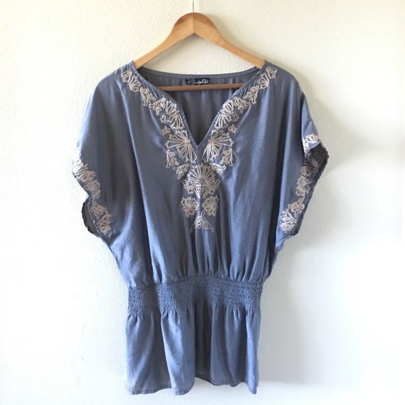 women's top. 85% Cotton 15% Polyester. Excellent condition. Made in China. Dressy top with a cute unique stitching design. Top is silver shiny material. Elastic around the tummy part of shirt. Mustard Seed Tops