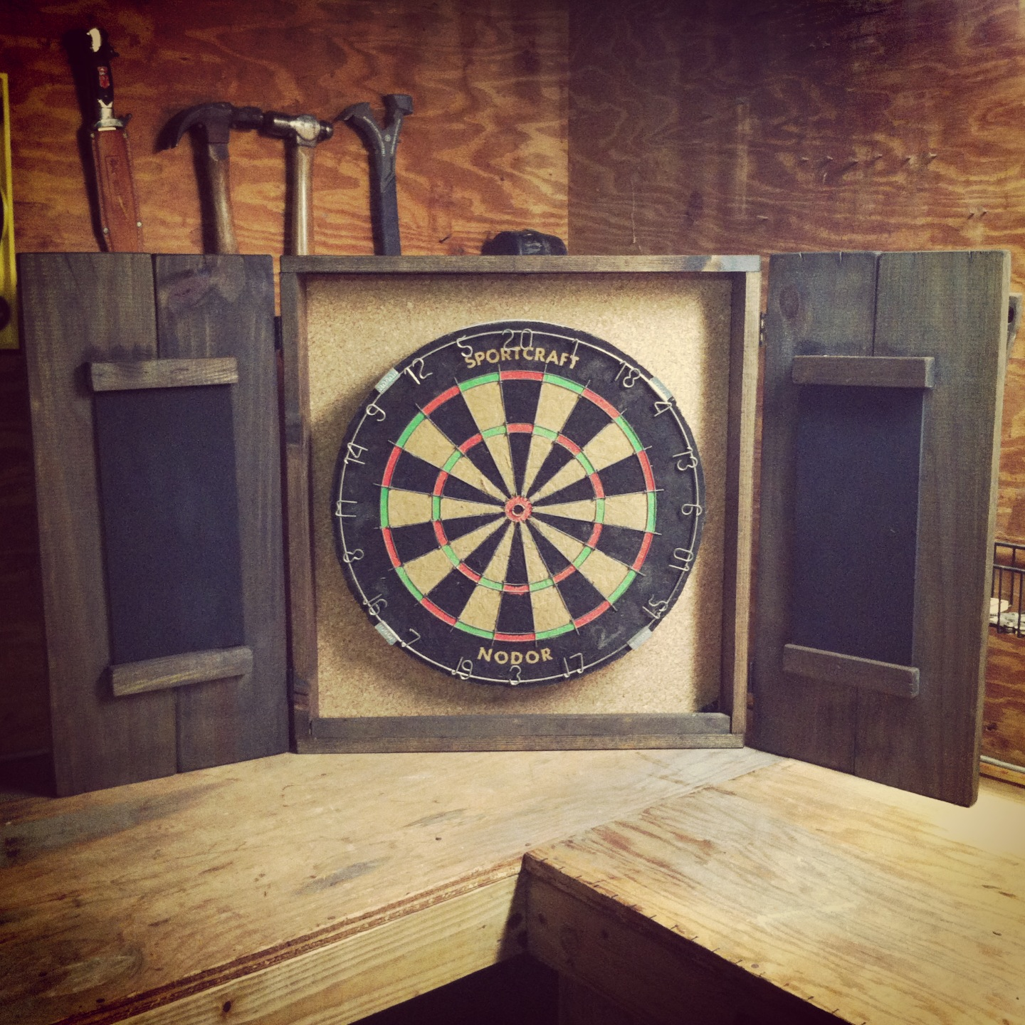 Dart Board Cabinet With Engraving On The Outside And Maybe White Chalk Is Annoying