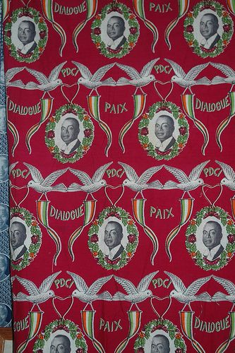 """Houphouët-Boigny (1960s? Cote d'Ivoire) featuring President of Cote d'Ivoire (1960-93). Shows slogan """"Peace, Dialogue"""" of the Parti Démocratique de la Côte d'Ivoire — Rassemblement Démocratique Africain, PDCI-RDA. Wine red, with dark red, orange, green. Image of Houphouët-Boigny is from either his Nov. 1960 election or the August 1960 independence. Suggests this might be from the 1965 or 1970 elecions. Would seem outdated in 1975, 80. No printing on selvage edge to give further clue. 2 yrds."""