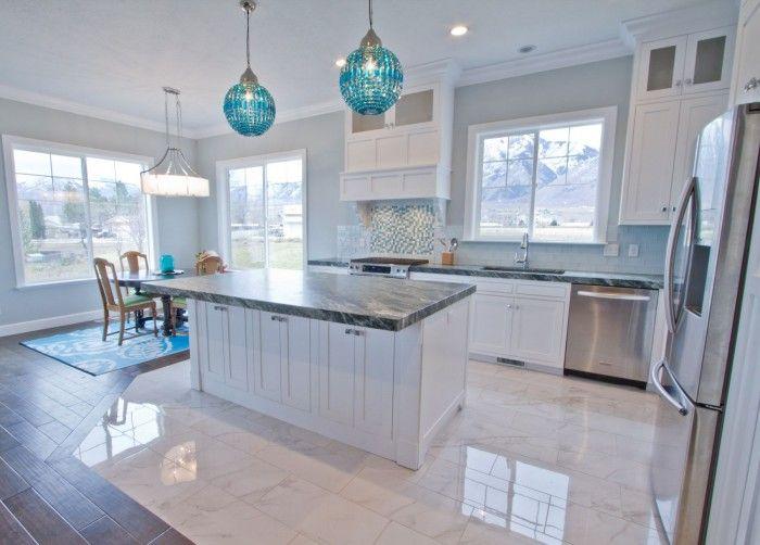 Elegant Coastal Kitchen Decor With White Island With Grey Granite Counter Top Featuring Splendid Blue Hanging Lanterns