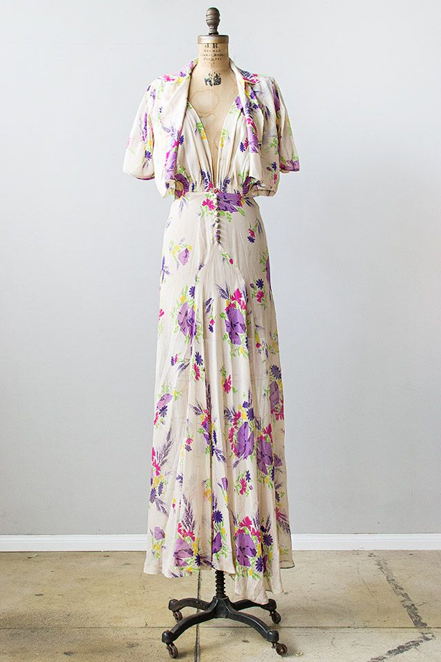 1930s off-white sheer floral silk crepe de chine maxi dress is cut on the bias and features flowing skirt, fabric covered buttons along the front, and deep v-neck front and back. Back of dress features smocking detail along the bottom of the bodice. Bodice is billowy and slightly blouson. Comes with matching short sleeve bolero with small collar that doesn't have any closures. Via Adored Vintage.