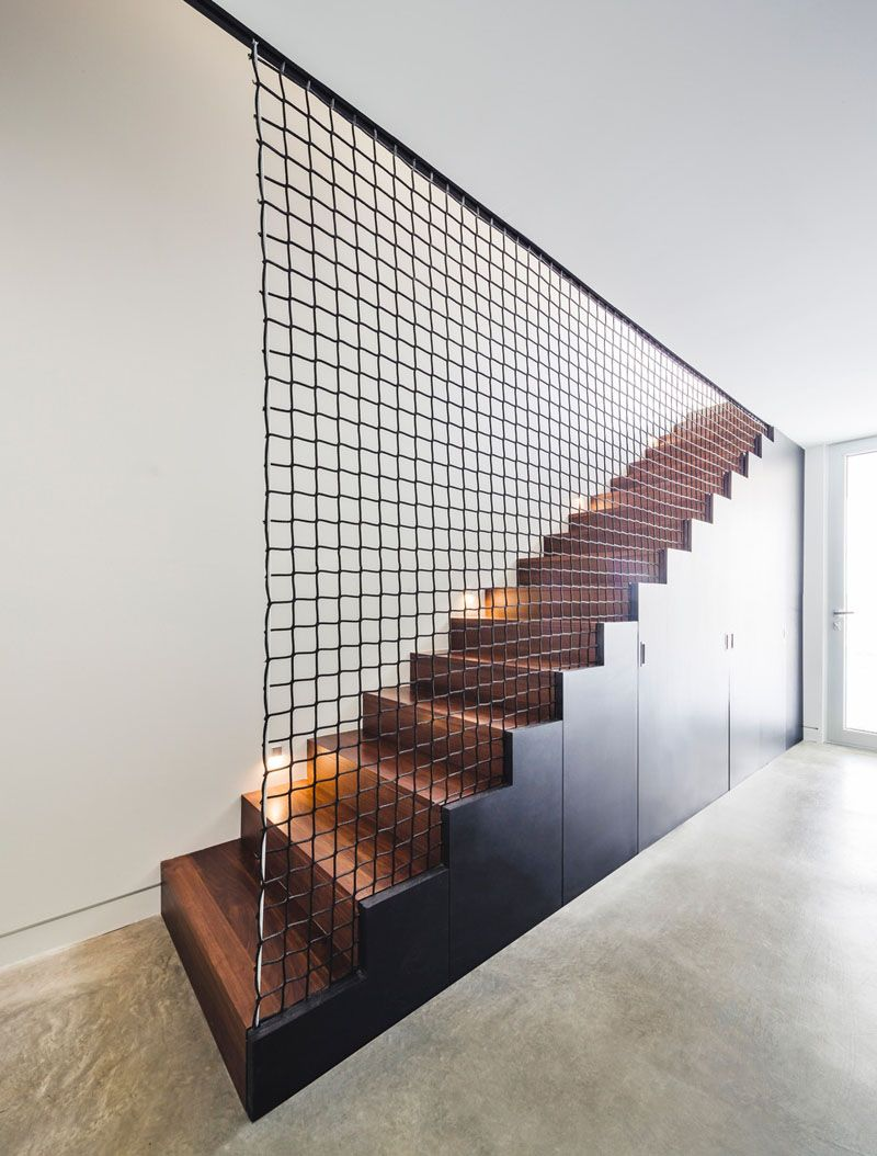 These black and wood stairs have storage built into them, and a wire ...