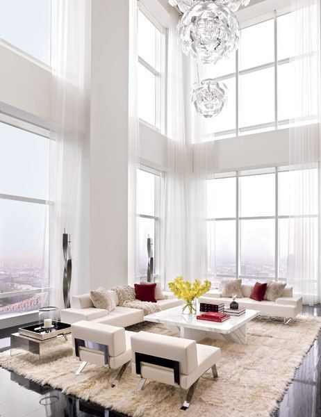 A Luceplan USA light fixture shimmers in the double-height living room of a Manhattan penthouse by ODA-Architecture, which is painted in a Benjamin Moore white and hung with curtains of a Sahco fabric; Poltrona Frau sofas join a marble cocktail table custom designed by Yutaka Takiura, and the floor lamps, side table, and Angora-goat-skin rug are from DDC.Pin it.