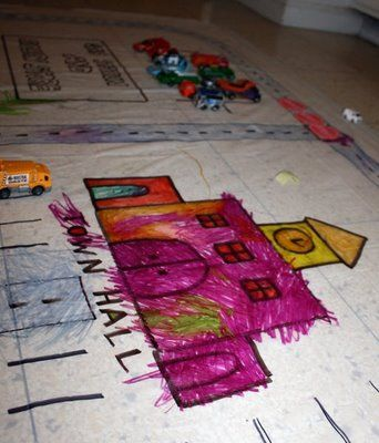 It's a shower curtain (liner) taped to the kitchen floor. The road is drawn on with permanent marker and the kids can color to their hearts content then drive their cars on it.  I like this, because it allows the children to do a lot of the creating!