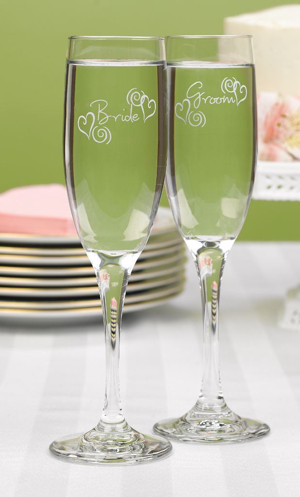 """Glass wedding champagne flutes with white heart and flourish design around Bride and Groom. Champagne flutes measure 8 3/4"""" tall and holds 6 ounces. Personalize with names and date or a single initial on back. Set of two."""