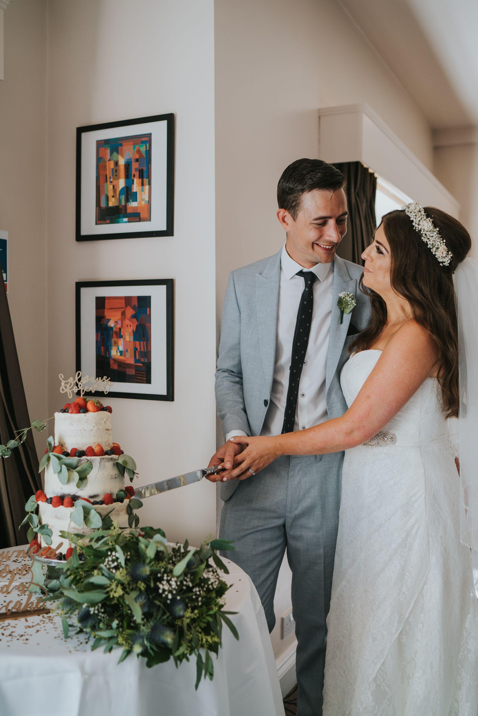 Smiling cake cutting portrait of bride and groom naked wedding cake