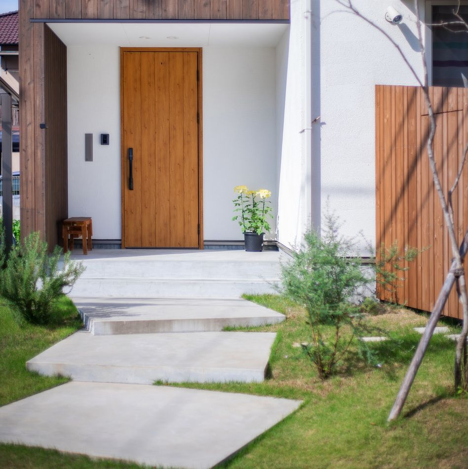 玄関前のアプローチの作り方で お家の印象はがらりと変わります こちらは 真四角のコンクリートを段違いに 並べたかのような一味違ったアプローチ 外観の雰囲気に合わせて作り込むことで おしゃれに仕上がります 外観 ファサード 庭 アプローチ コンク