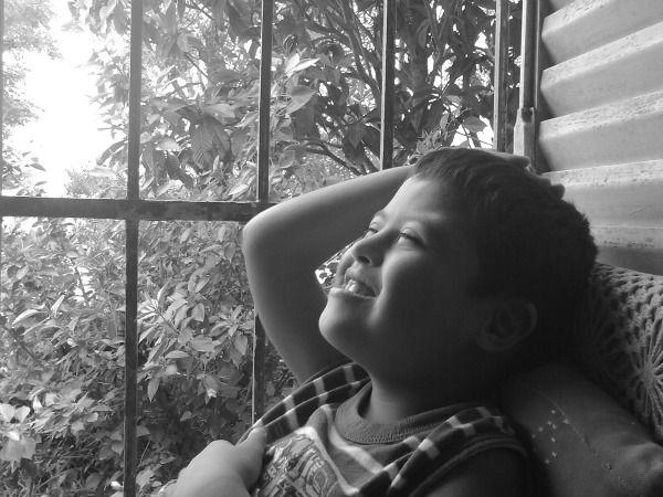 Foto de niño con síndrome de Down reflexionando feliz