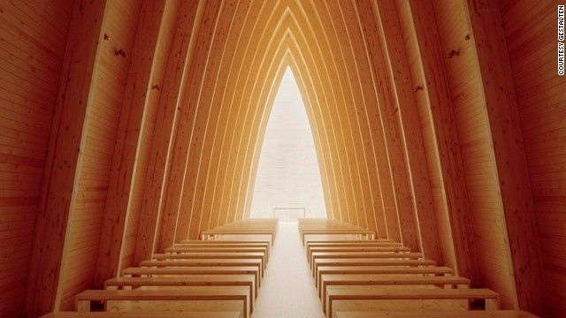 Step inside and you'll find the arched pine wood ribs leading to a back-lit alter. Designed by Sanaksenaho Architects.