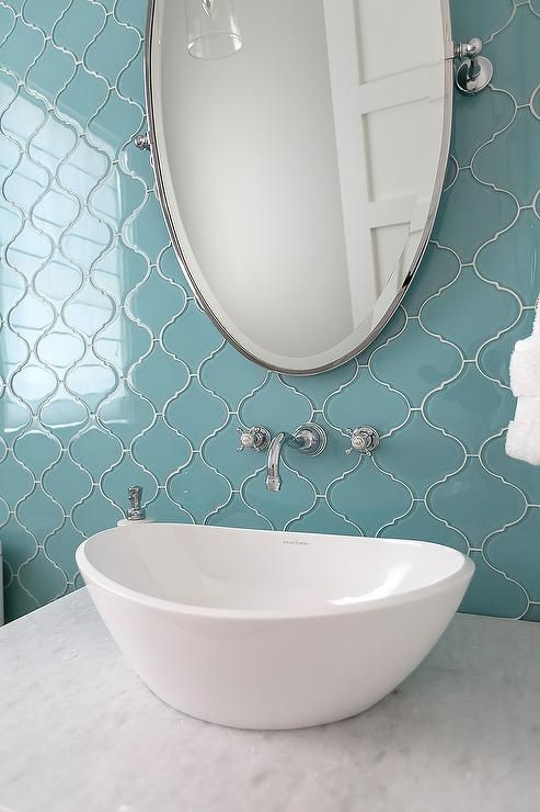 Gorgeous blue and white powder room features an oval pivot vanity mirror fixed on ann sacks glass tile also lovely is illuminated by  moravian star