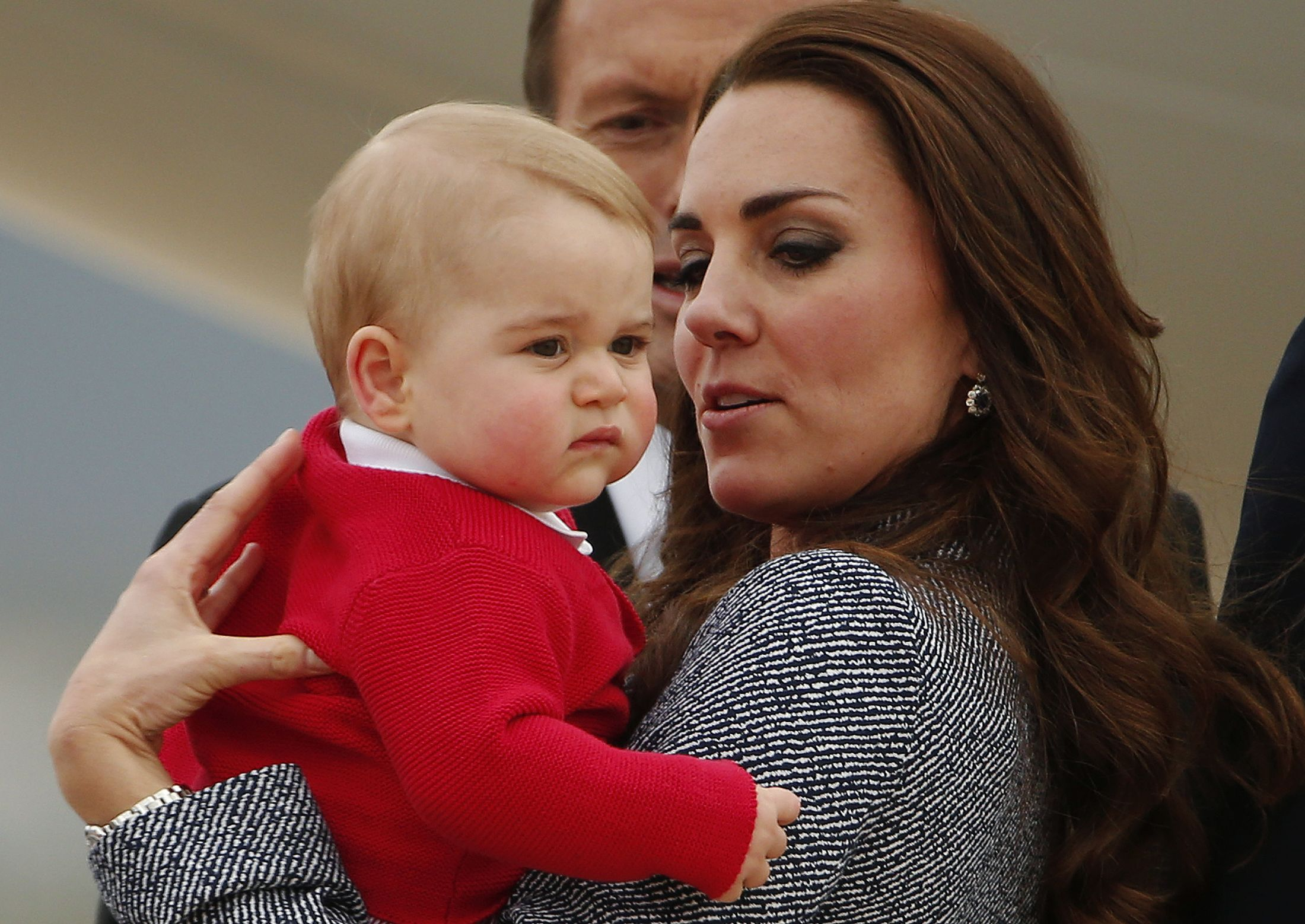 Britain's Catherine, the Duchess of Cambridge, holds her son Prince George as they prepare to board a plane with her husband Prince William (not pictured) to depart Canberra April 25, 2014. The Prince and his wife Kate are undertaking a 19-day official visit to New Zealand and Australia with their son Prince George. (REUTERS/Phil Noble)