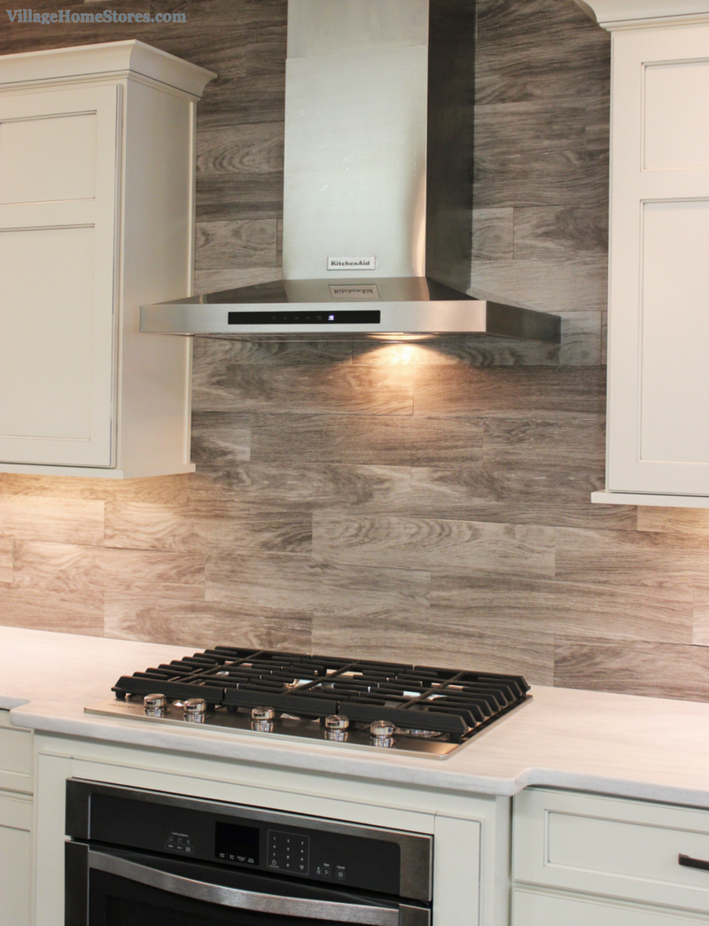 Porcelain floor tile with a gray woodgrain pattern is installed as a backsplash in this Kitchen tile backsplash