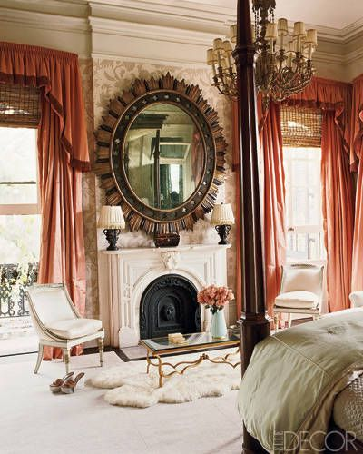 Decorator Richard Keith Langham gave tradition a feminine twist in the master bedroom of a family's New Orleans home. An antique gilt-wood mirror is set against a wall covering with a floral print. The lush curtains are offset by simple reed shades.