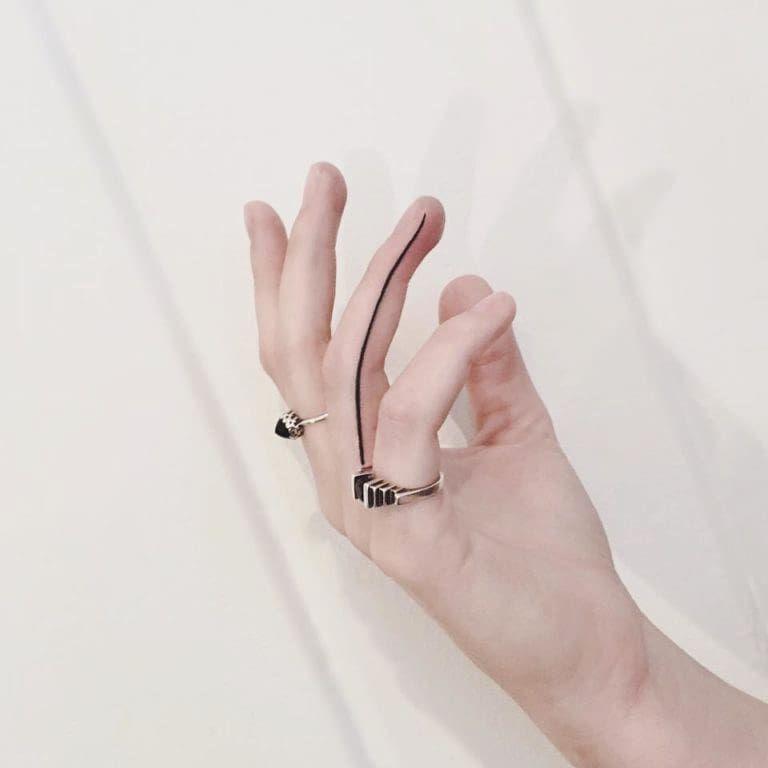 Photo of Fine ligne noire tatouée sur l'annulaire de la main droite