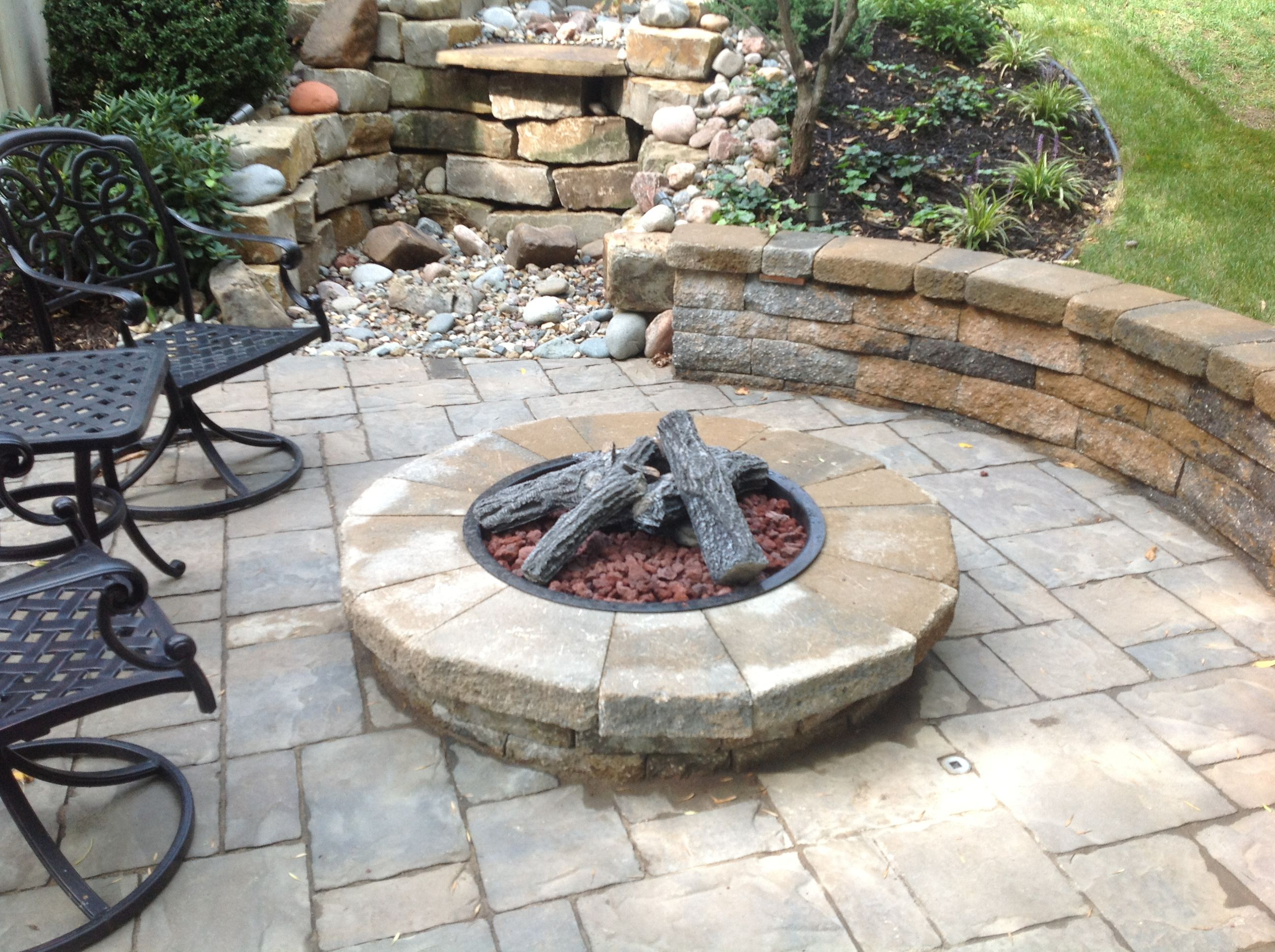 the combination of the fire pit retaining wall and landscaping