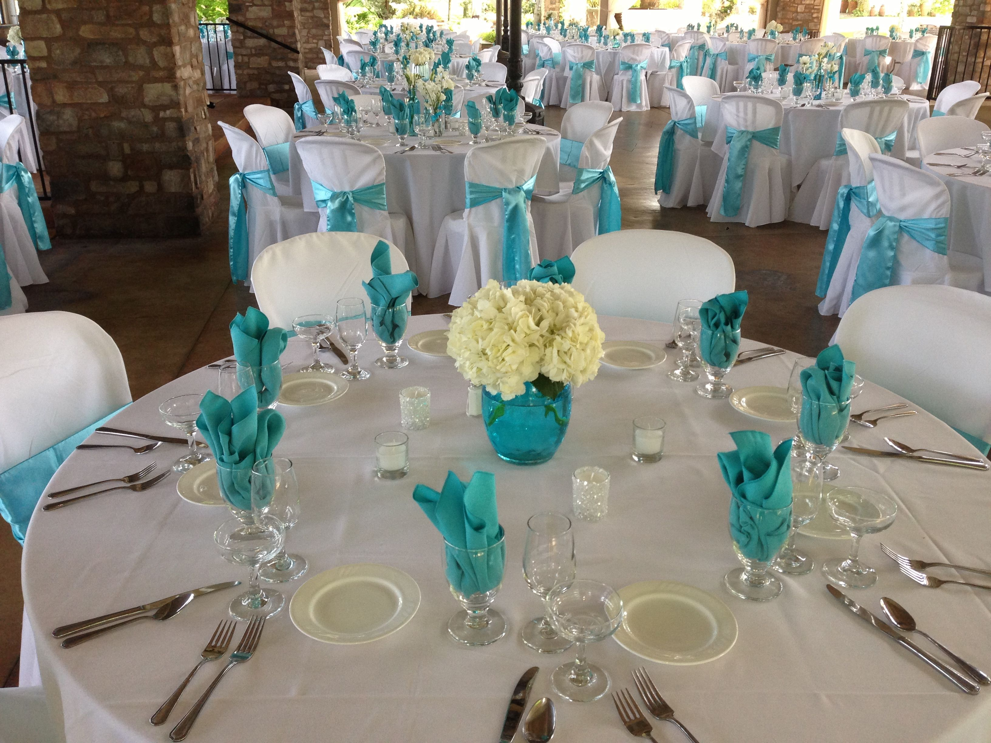 White hydrangea in aqua blue vessel centerpieces