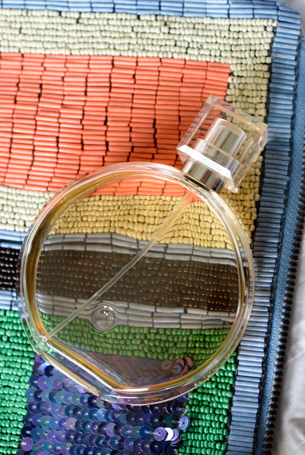 Pretty perfume bottle on a multicolored striped beaded clutch.