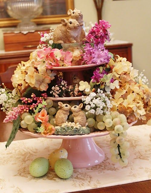 Fill three tiered cake stands with  faux flowers, grapes and bunnies. Oh, they were Easter bunnies because they brought some eggs! :)