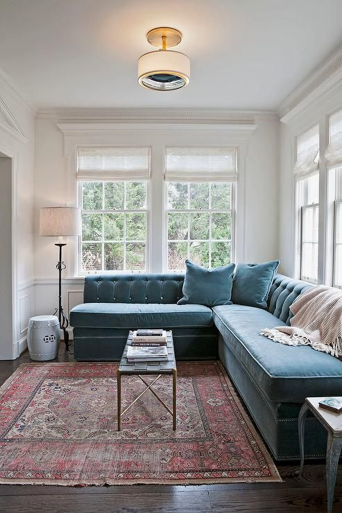 Transitional living room features a peacock blue velvet tufted sectional placed under windows dressed in white roman shades facing a slim black basket weave coffee table atop a red kilim rug.