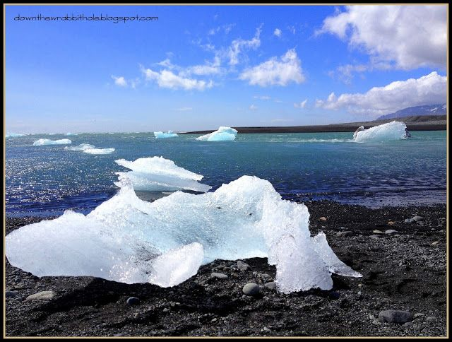 """Icebergs on a black sand beach on the North Sea at Jokulsarlon, Iceland. Find out more at """"Down the Wrabbit Hole - The Travel Bucket List"""". Click the image for the blog post."""