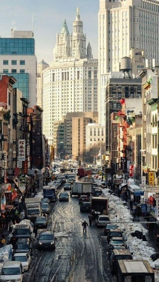 Traffic and stores along East Broadway in New York City's Chinatown, leading towards the Municipal Building