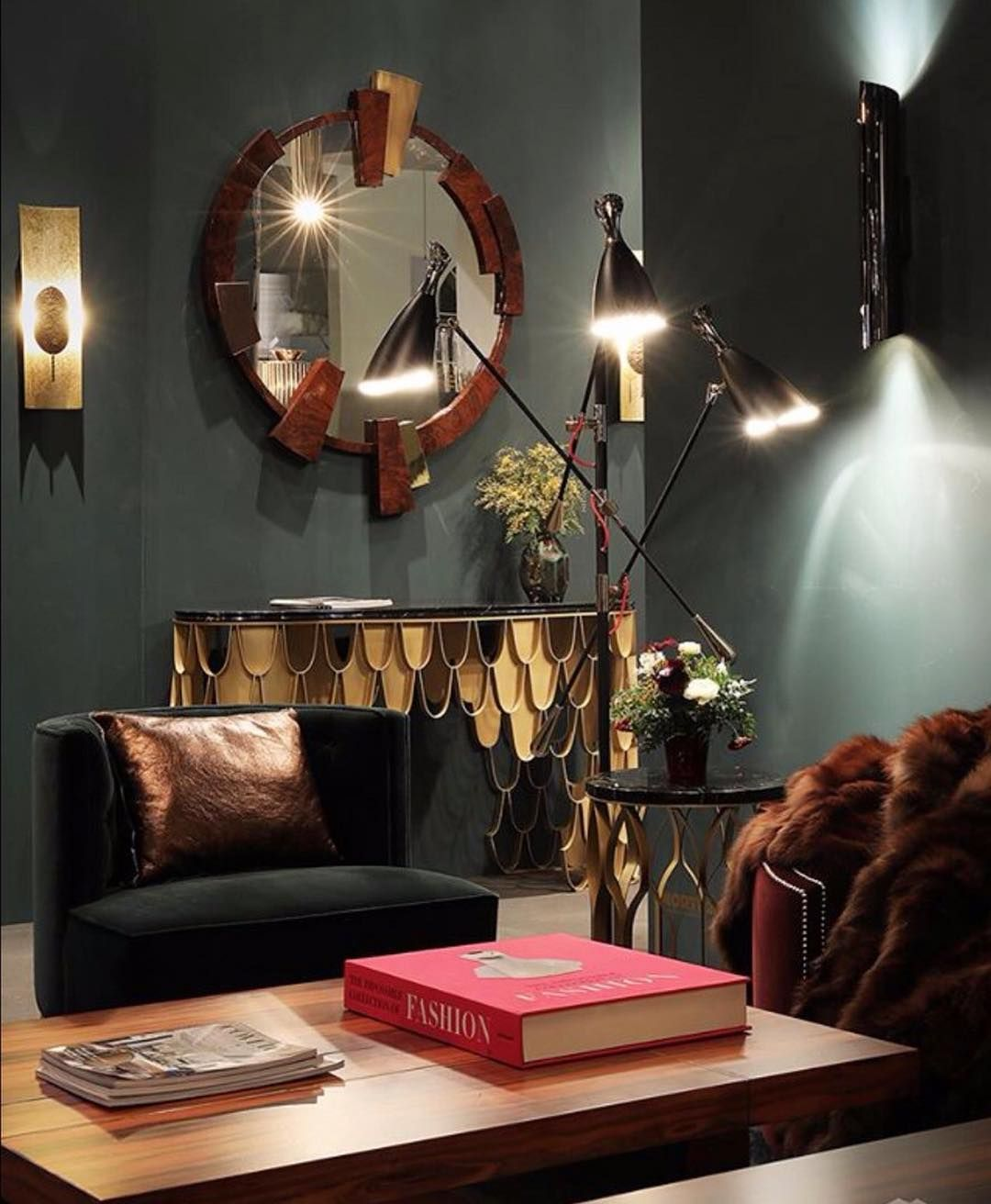 Create a moody yet sophisticated vibe with dark walls strategic lighting and brass furniture with a pop of colour courtesy of assoulines impossible