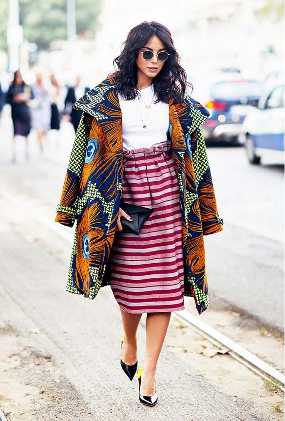 mastering mixed prints in a high-waisted striped skirt, white t-shirt, printed coat and circle sunglasses