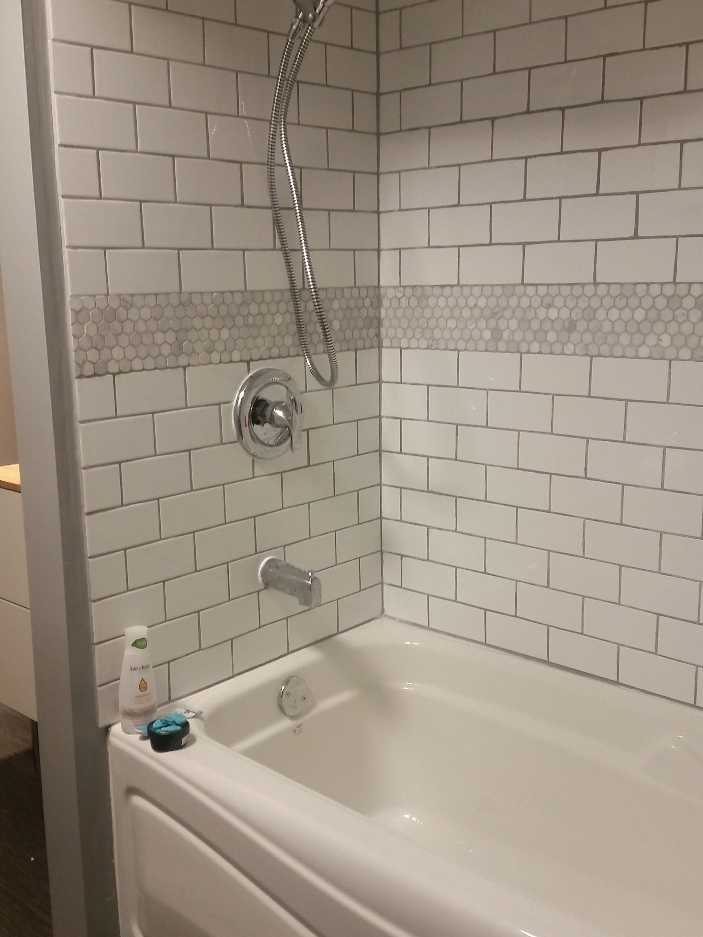 White subway tile bathtub surround with marble hex tile ...