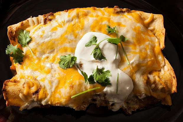 A slow cooker Mexican enchilada recipe with pulled pork, a long-cooked chile sauce with tomatoes, cheddar, and Monterey Jack cheese, cilantro, and sour cream.