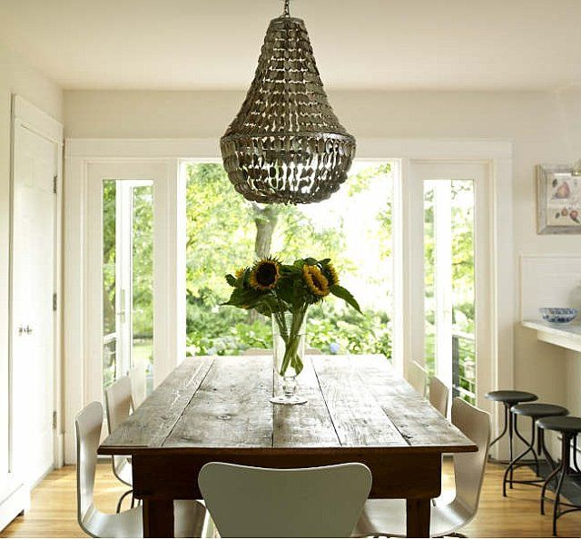 The dining room of bella mancinis greenport beach house features a shell chandelier that bridges her farm table and modern chairs perfectly