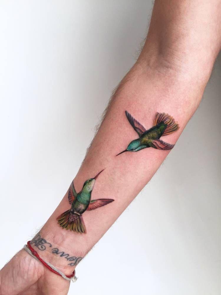 Two illustrative hummingbirds on Jonni's right inner forearm.