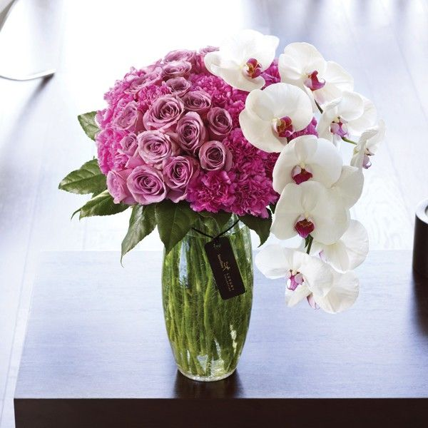 Luxury Rose and Phalaenopsis Orchid Vase: The height of sophistication, this striking vase arrangement is a magnificent gift choice. Two exquisite stems of Phalaenopsis orchid are perfectly contrasted by a bed of superb carnations and large-headed roses in pink and lilac tones. This lavish vase arrangement is a pleasure to behold.