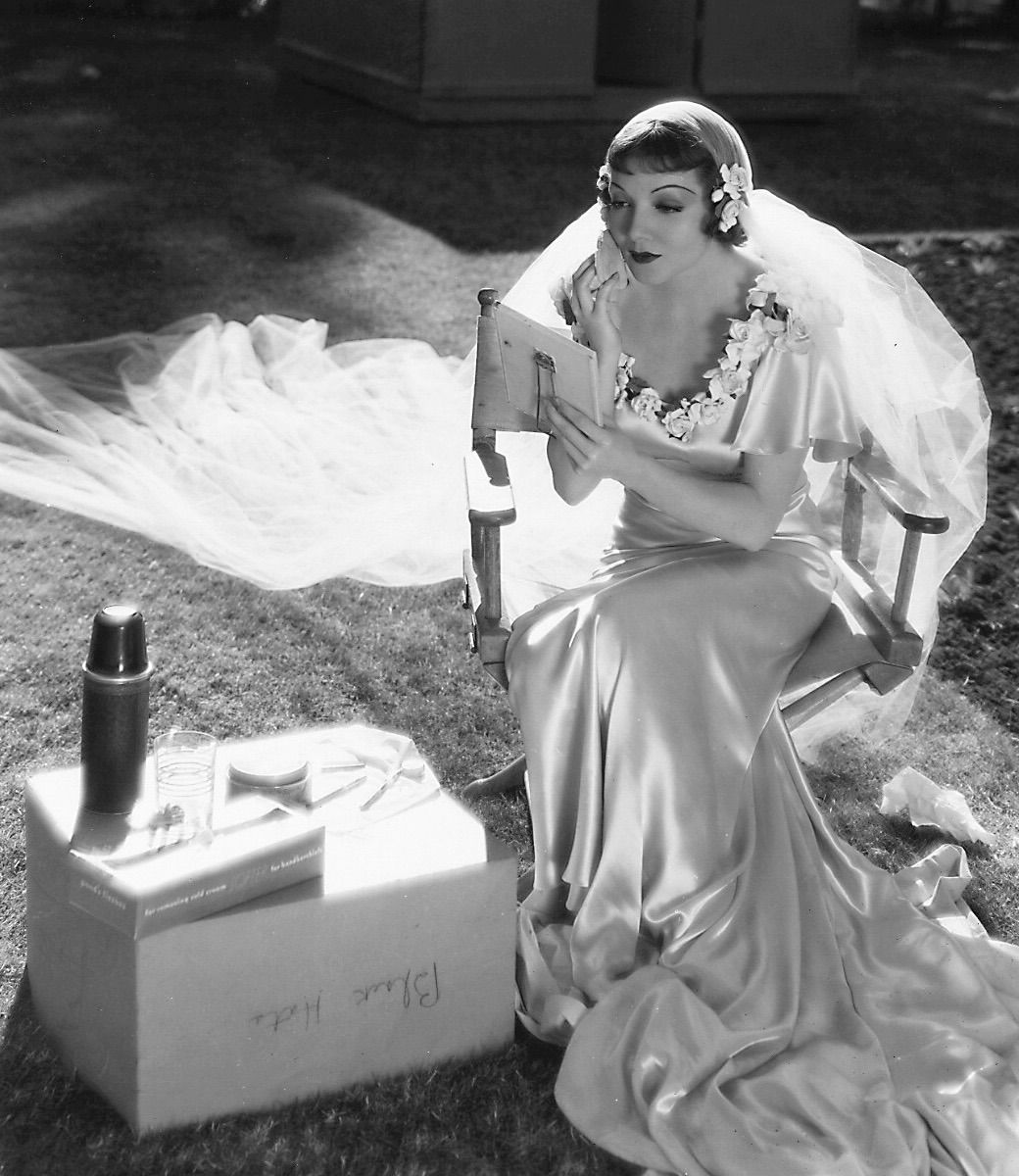 Claudette Colbert touching up her makeup on the set of It