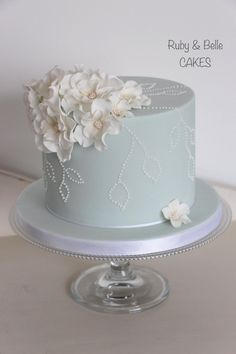 Single tier celebration or wedding cake with delicate frilly flowers and piped dot detail. We love this cake with the addition of matching cupcakes also! By Ruby & Belle Cakes, Brighton, UK