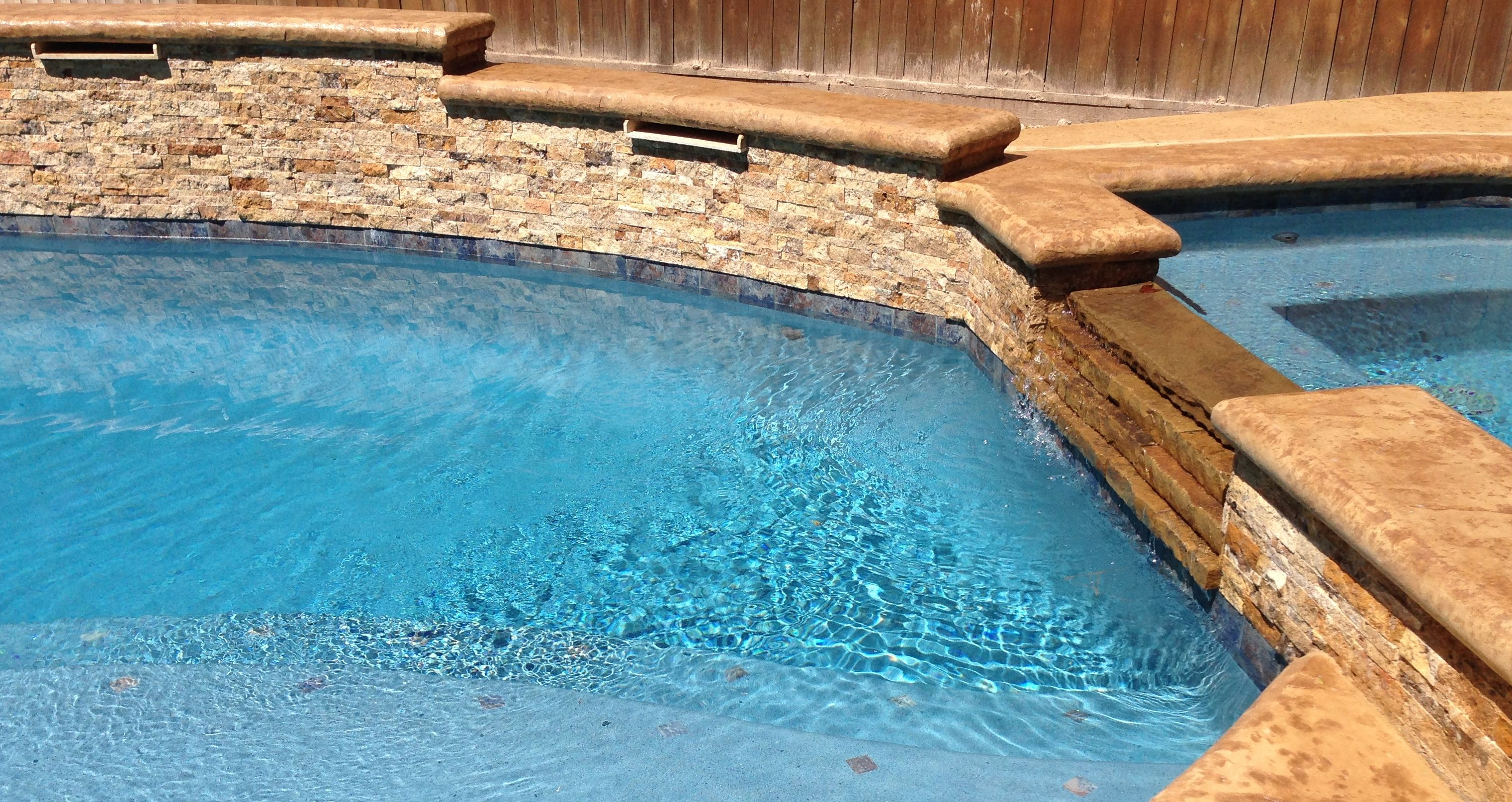 Swimming Pool Raised Wall With Ledger Stone And Concrete Cantilever Stamped Coping Scupper Flagstone Pool Decks Travertine Pool Decking Pool Water Features