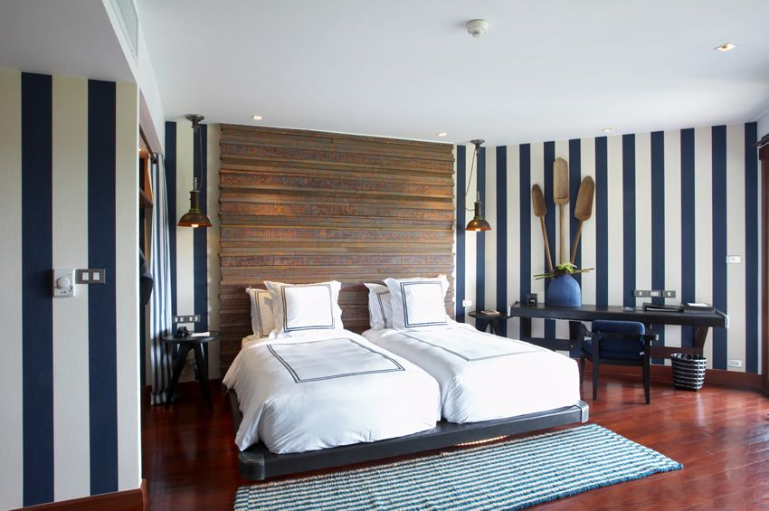 Nautical themed bedroom with striped walls and hardwood floors.