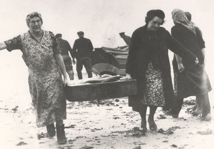 Two fisherwomen carrying fish boxes along the shore at Newbiggin by the Sea, Northumberland. c. 1950