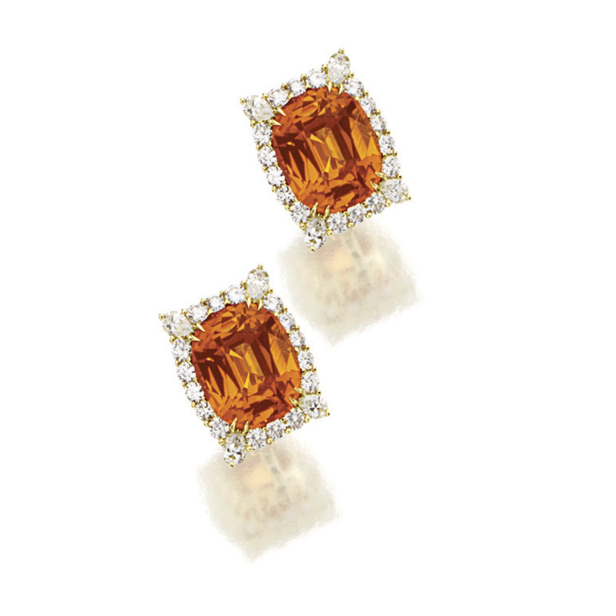"""PAIR OF SPESSARTINE GARNET AND DIAMOND EAR CLIPS. Each set with an oval spessartine garnet altogether weighing approximately 18.88 carats, encircled by brilliant-cut diamonds, within a stylised diamond-set basket, the diamonds altogether weighing approximately 2.15 carats, mounted in 18 karat yellow gold, clip and post fittings, signed """"Agapoff""""."""