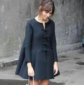 Alexa Chung. Una invitada muy lady con vestido abrigo negro con vuelo desde la espalda