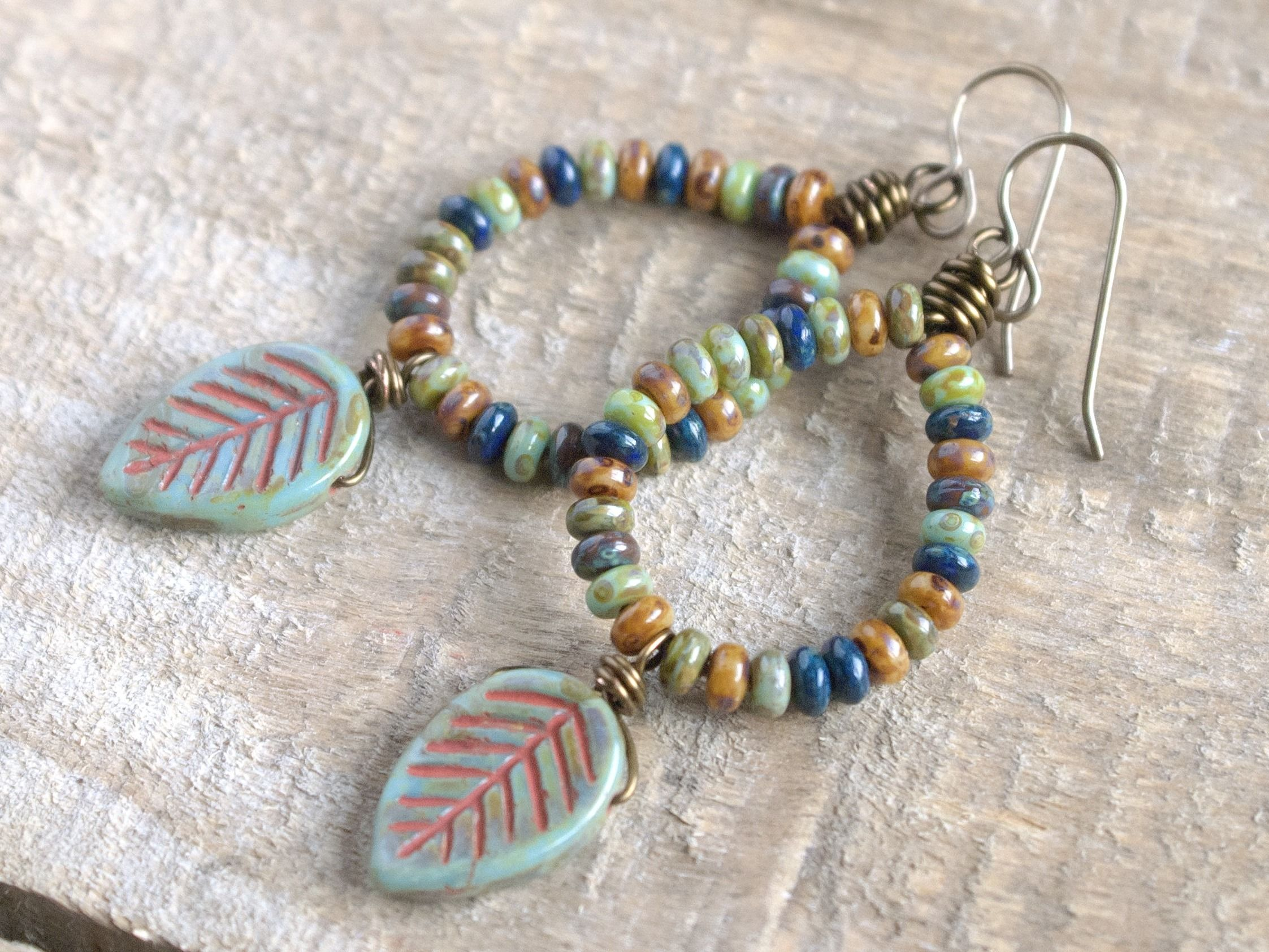 This pair of long, boho style earrings are just perfect for Autumn! They have been made using rustic turquoise-green Czech glass leaf beads. The leaves have a rusty red Picasso finish which highlights their beautiful carved pattern. Above the leaves are Czech glass donut beads in earthy shades of brown, olive, mustard and navy. These tiny beads have been strung one by one onto hand formed wire hoops.