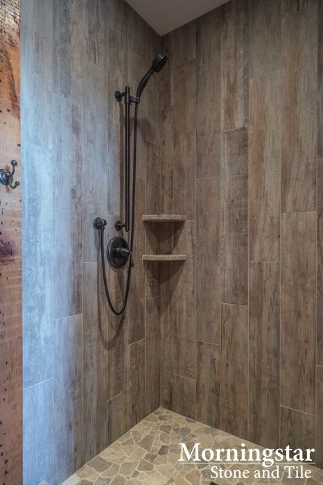 Shower stall with wood like tile that has a rustic yet for Cabin shower tile ideas
