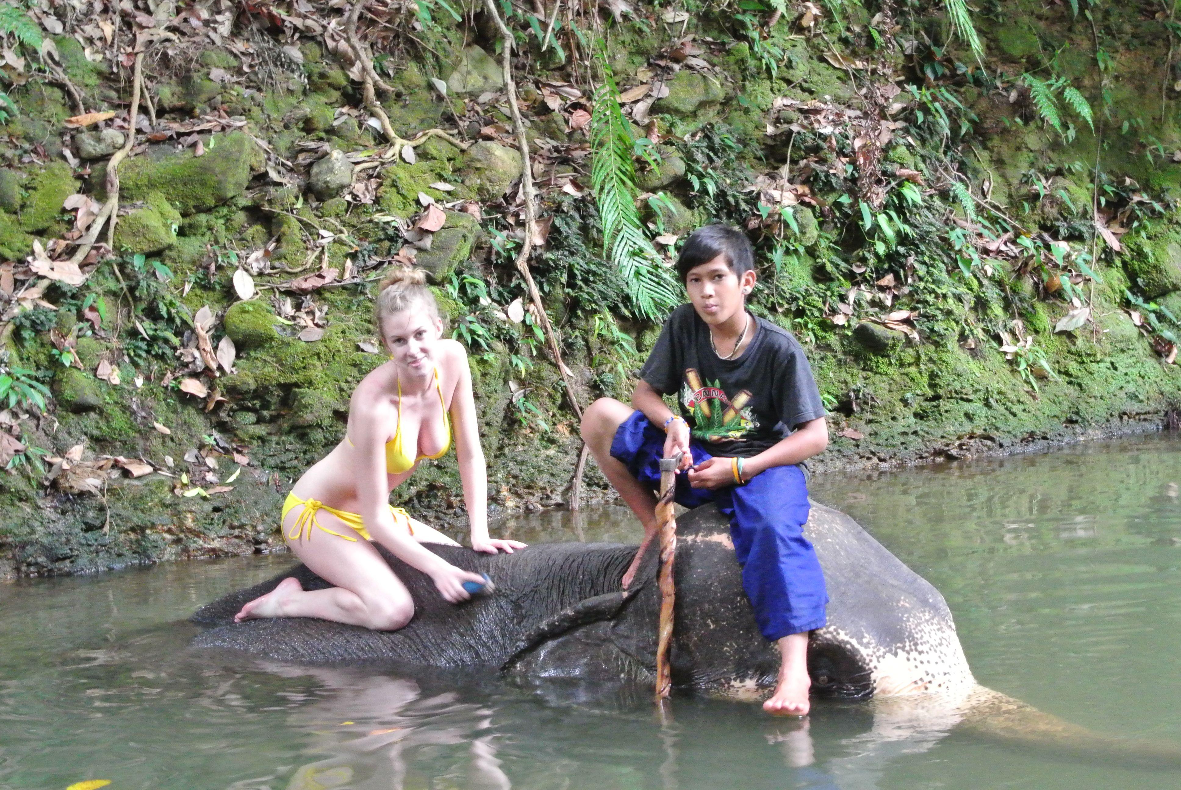 Sexy Woman in bikini washing an Elephant in the Jungle/Sexy Frau im bikini wäscht einen Elefant im Dschungel .