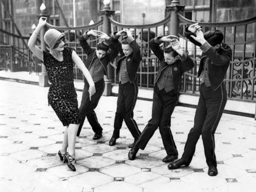 firsttimeuser:    American woman teaching English boys to dance the Charleston. Great Britain, 1925