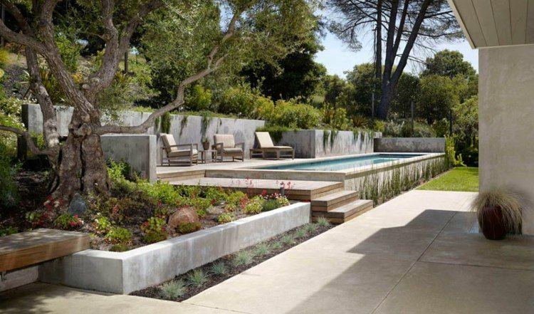 terrasse sur terrain en pente piscine rectangulaire fauteuils en bois arbres et banc en bois