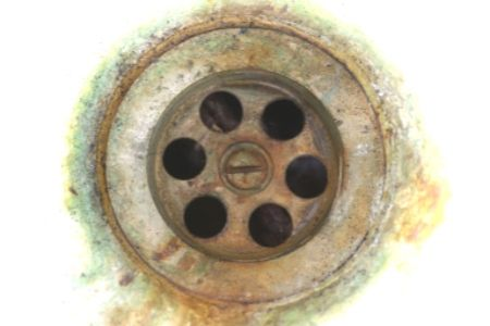 Muriatic acid is very effective for cleaning drains, although it should probably only be used as a last resort.