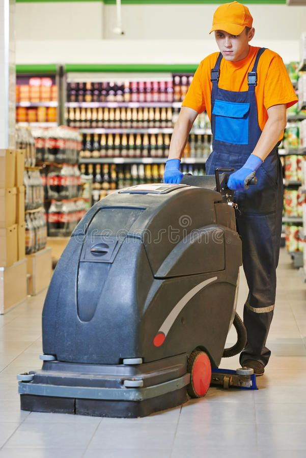 Worker cleaning store floor with machine. Floor care and cleaning services with ,
