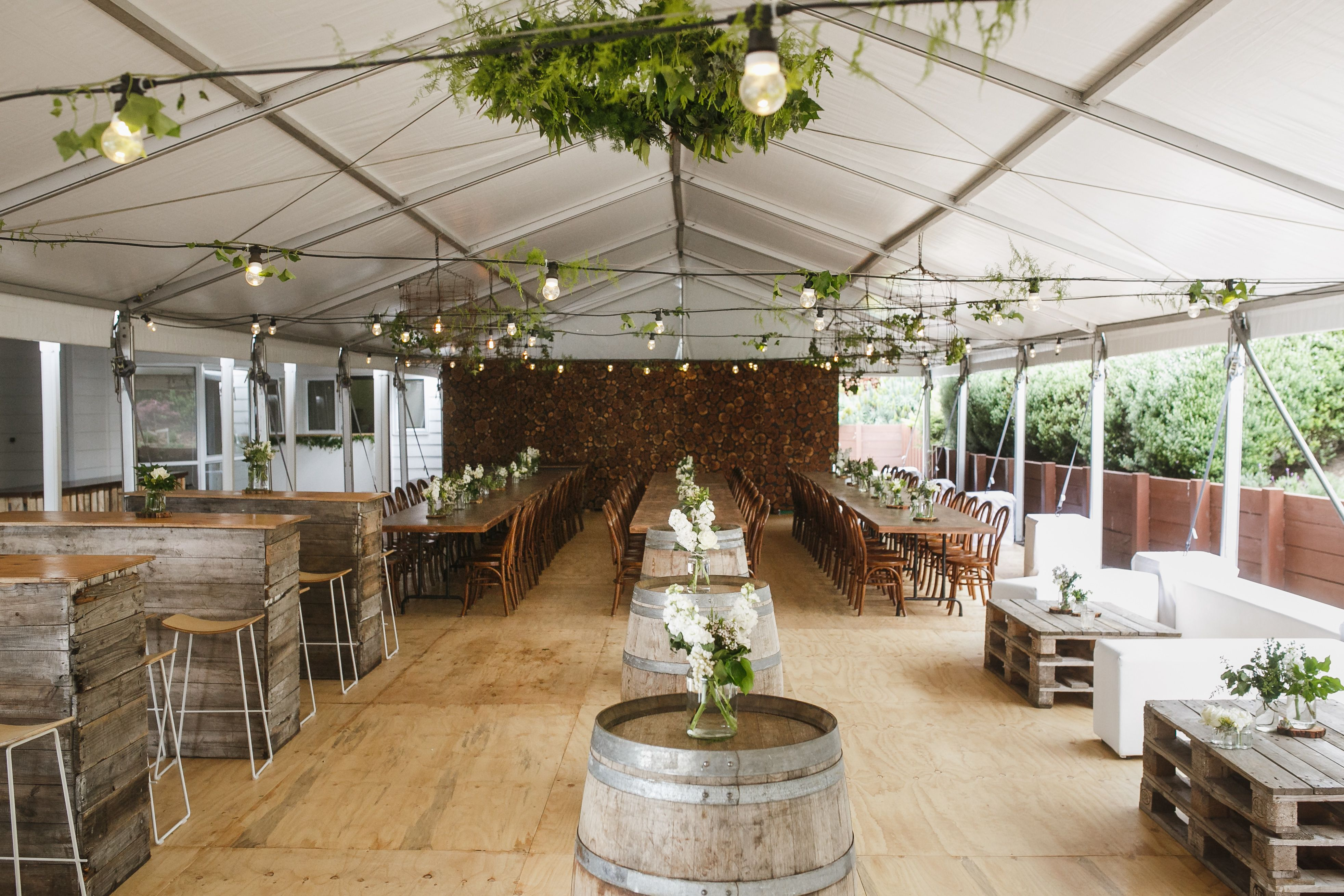 Rustic backyard marquee wedding wine barrels pallet furniture ottomans timber trestle tables and bentwood chairs hire and styling by over the top events