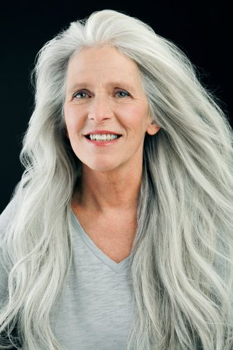 Mature woman in her sixties in front of black background for Gorgeous in gray